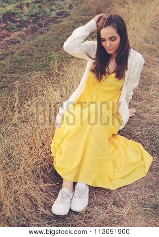Young woman outdoor portrait sitting on a deadwood autumn field.
