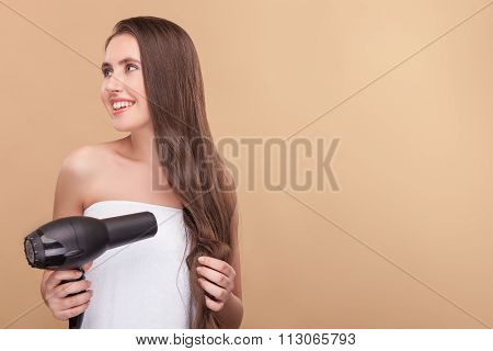 Cheerful healthy girl is using modern hairdryer