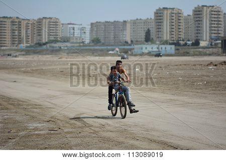 Two boys riding a bike on beach in Sumgait, Azerbaijan