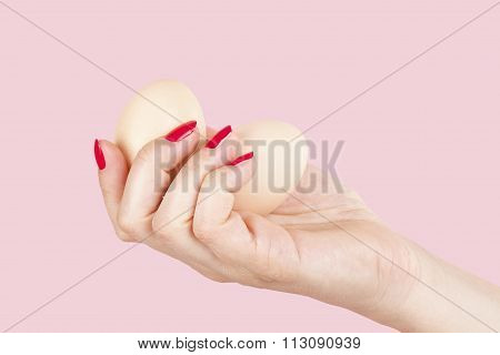 Female hand with red fingernails holding two eggs isolated on pink background. Feminism emancipation provocation and relationship problems. poster