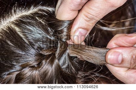 Closeup Of A Hairdresser Braiding Hair
