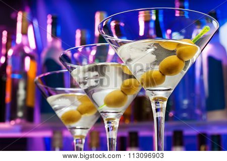 Olives in cocktail glasses and bar bottles