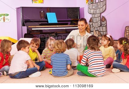 Group of kids sit and listen to teacher tell story