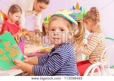 Girl glue paper in crafting kindergarten