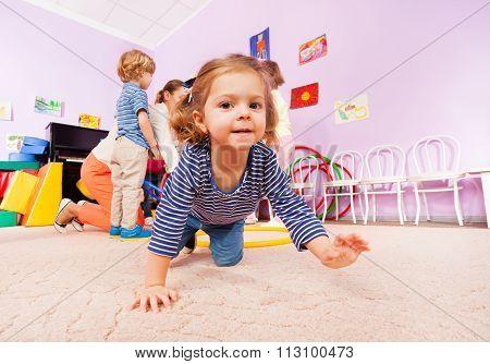 Girl crawl on active class lesson in kindergarten