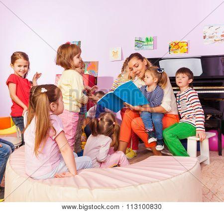 Boys and girls listen to teacher read book