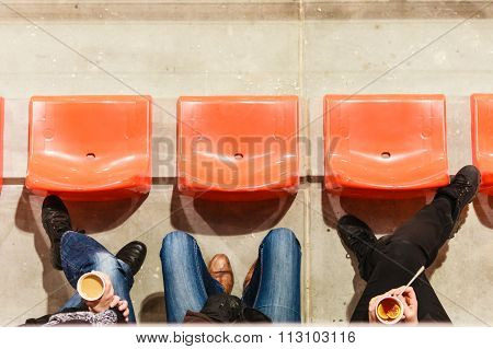 Row Of Plastic Chairs And Legs In Football Stadium.