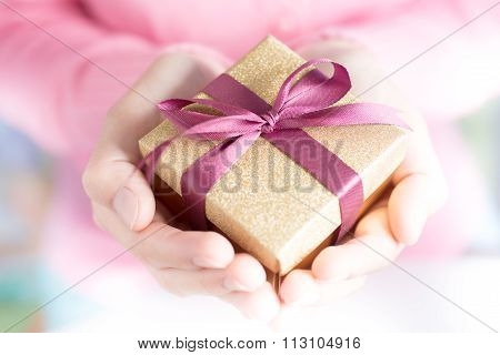 Close up of hands holding a small gift wrapped with pink ribbon. Small gift in the hands of a woman indoor. Shallow depth of field with focus on the little box.