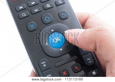 Finger Will Push Ok Button On Remote Control Over White Background