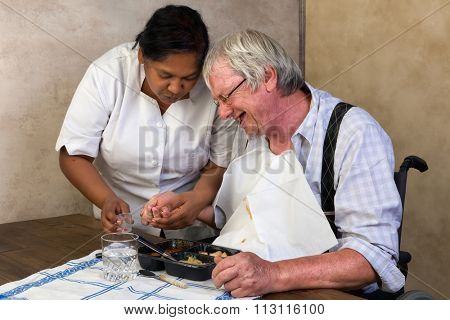Nurse in old people's home trying to make a patient eat his dinner and pills