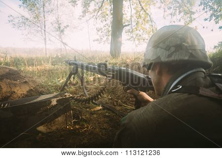 Re-enactor dressed as german wehrmacht soldier aiming a machine