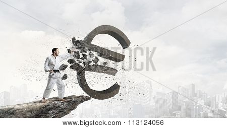 Young determined karate man breaking with hand concrete euro sign