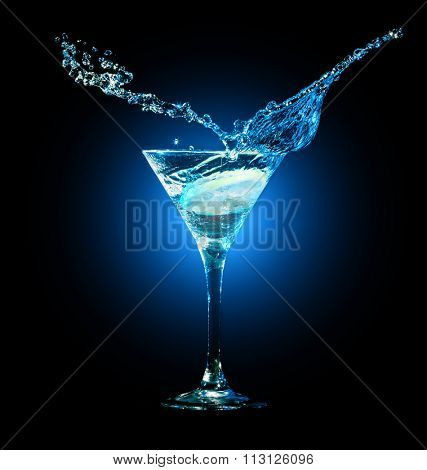 cocktail in glass with splashes and lemon on dark background. Party club entertainment. Mixed light