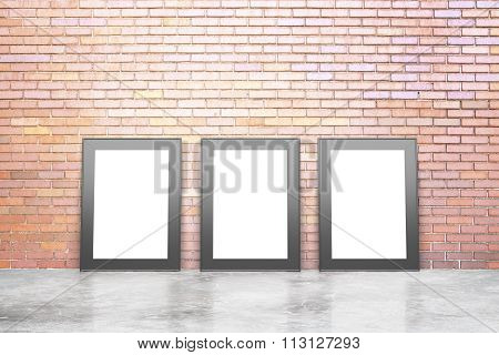 Blank White Picture Frames In Empty Loft Room With Concrete Floor And Red Brick Wall, Mock Up