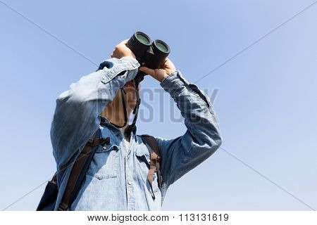 Young Man looking though binoculars with clear blue sky