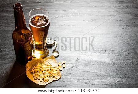 Beer With Peanuts On The Black Wooden Table. Free Space For Text.