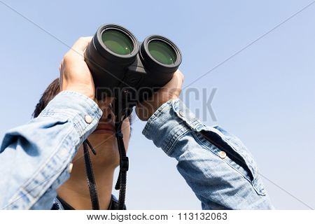 Man looking though binoculars with clear blue sky