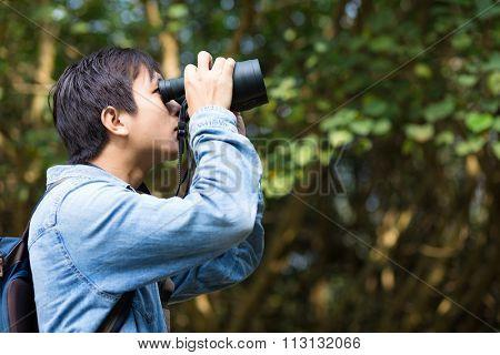The side profile of Man watching though binoculars