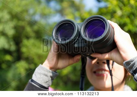Woman looking though binoculars at forest
