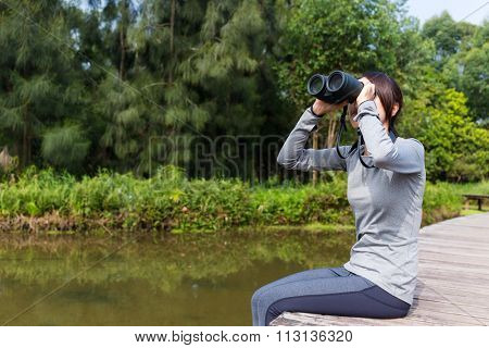 Asian woman watching though binoculars and sitting besides revier