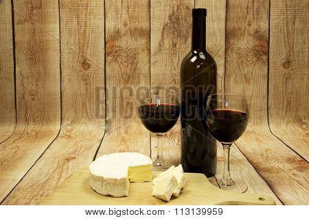 Two Wine Glasses With Red Wine,bottle Of Wine And Cheese On Wooden Table
