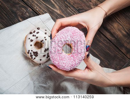 Female hand picking sweet sugary donut from rustic wooden kitchen table, top view