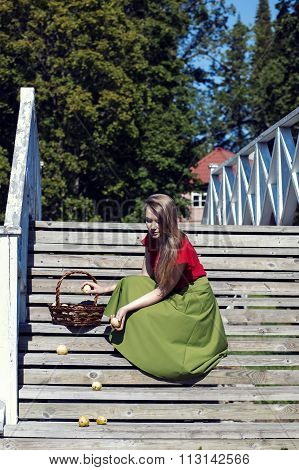Girl in long skirt collects dropped apples