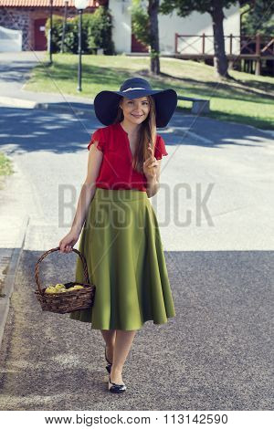 Happy village woman is carrying green apples