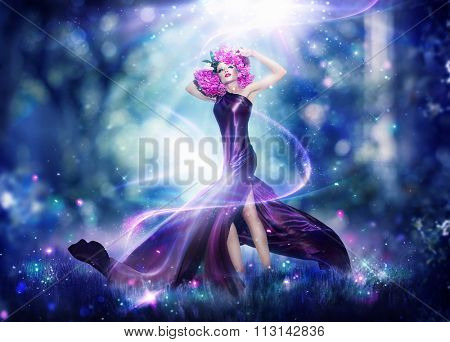 Beautiful Fantasy Fairy Woman, Fashion Art Beauty Portrait. Beautiful Girl in Fantasy Mystical and Magical Spring Garden. Model Woman wearing flowers wreath and Long satin dress making magic outdoor