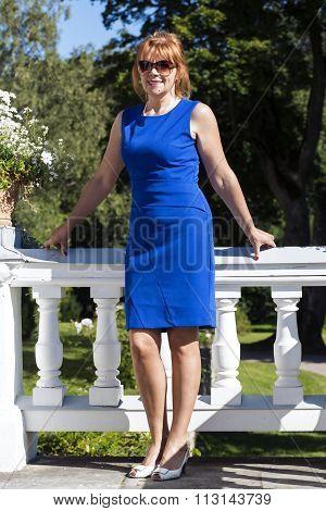 Female in a blue dress poses elegantly