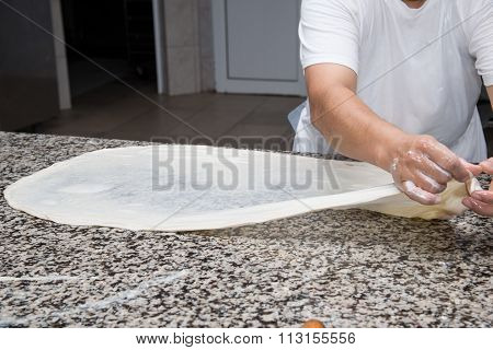 close up of female hands kneading dough and making banitsa - typical bulgarian pastry poster