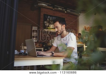 Small business owner developing new menu on laptop computer for his cozy cafe