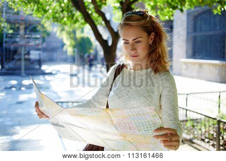 Young beautiful female tourist exploring city map while got lost in foreign city during summer trip