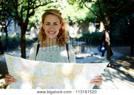 Young joyful woman with tourist map in hands enjoying beautiful strolling during her spring journey