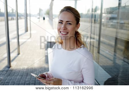 Happy smiling woman in urban setting using cell telephone for chat with friend
