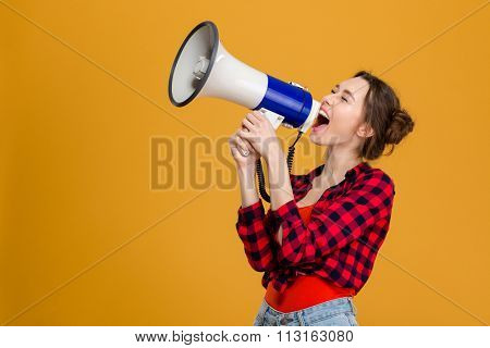 Funny excited young woman in checkered shirt shouting in megaphone over yellow background