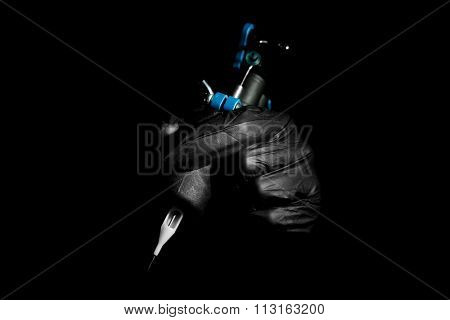 Tattoo artist holding tattoo machine on black background