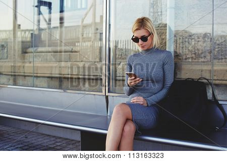 Woman with trendy look reading information on mobile phone while waiting outdoors on a her taxi