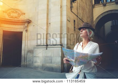 Young female student checking out the sights on atlas during trip overseas