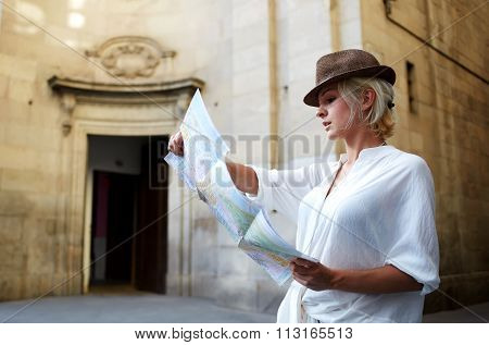 Attractive young female wanderer attentively studying local map during touring in the city