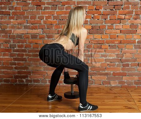 Athletic Woman In Black Leggins Performing Deadlift With Dumbbe