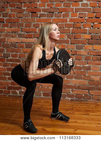 Attractive Athletic Woman In Black Leggins Performing Squatting