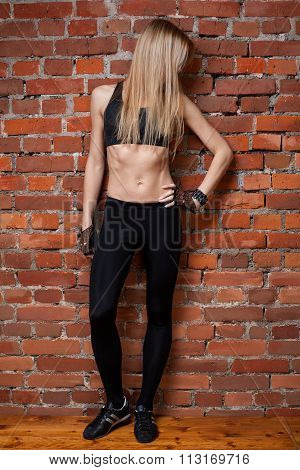 Young Blond Fitness Model In Black Top And Leggins  Head Is Turn