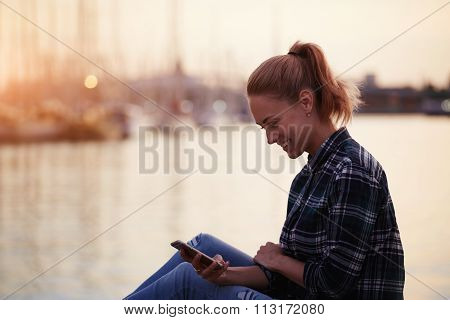 Cheerful hipster girl sitting on a pier near sea port and read pleasant text message