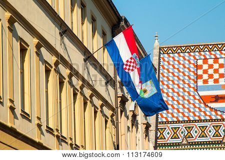 Flags of the Republic of Croatia and City of Zagreb on historic buildings on St Mark's Square in Zagreb, Croatia, roof of St Mark's church in background poster