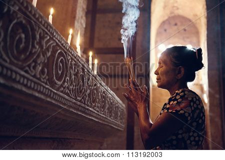 Old wrinkled traditional Asian woman praying with incense sticks inside a temple, low light, Myanmar poster