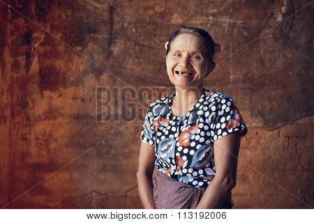 Portrait of traditional old Asian Burmese woman smiling, standing inside a temple, low light, Bagan, Myanmar