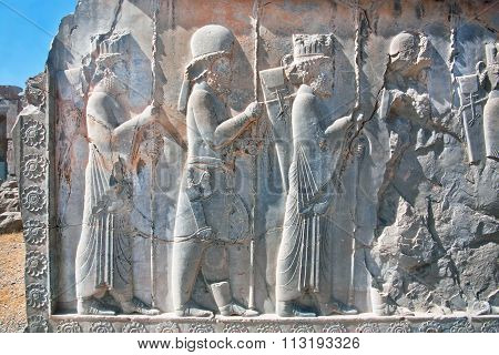 Silhouettes Of People In Ancient Costumes On The Destroyed Stone Bas-relief In Famous City Persepoli