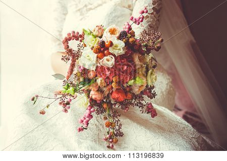 Bridal bouquet with red and burgundy flowers.