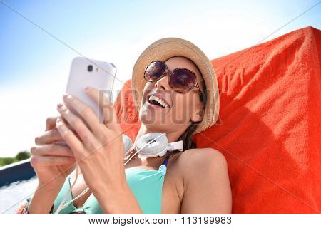 Cheerful funny girl relaxing in long chair with smartphone
